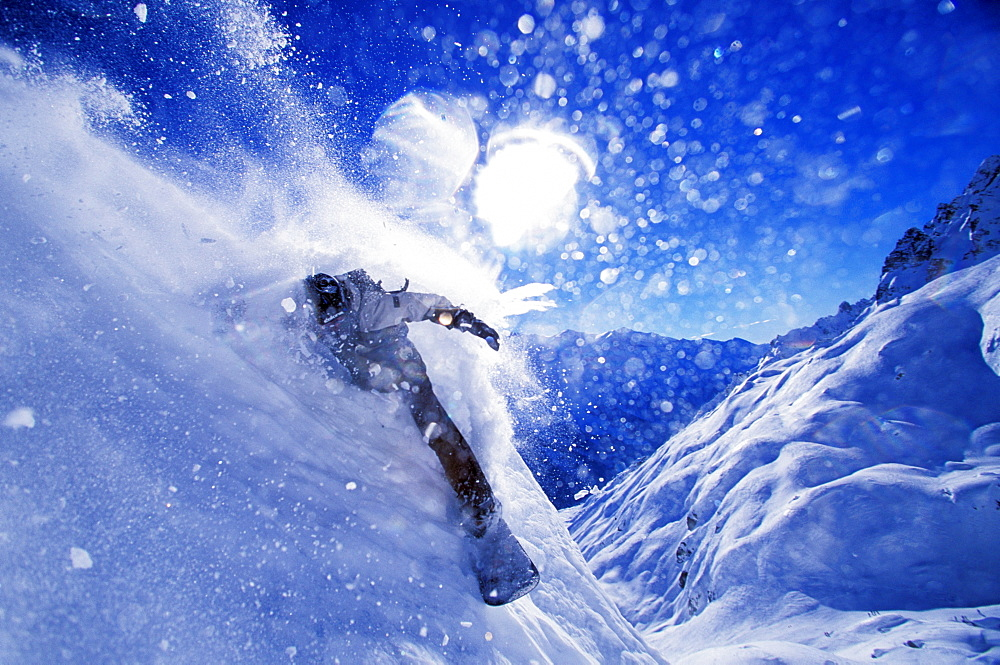 A snowboarder carves an 'in your face turn' while snowboarding on a sunny day in Chamonix, France.