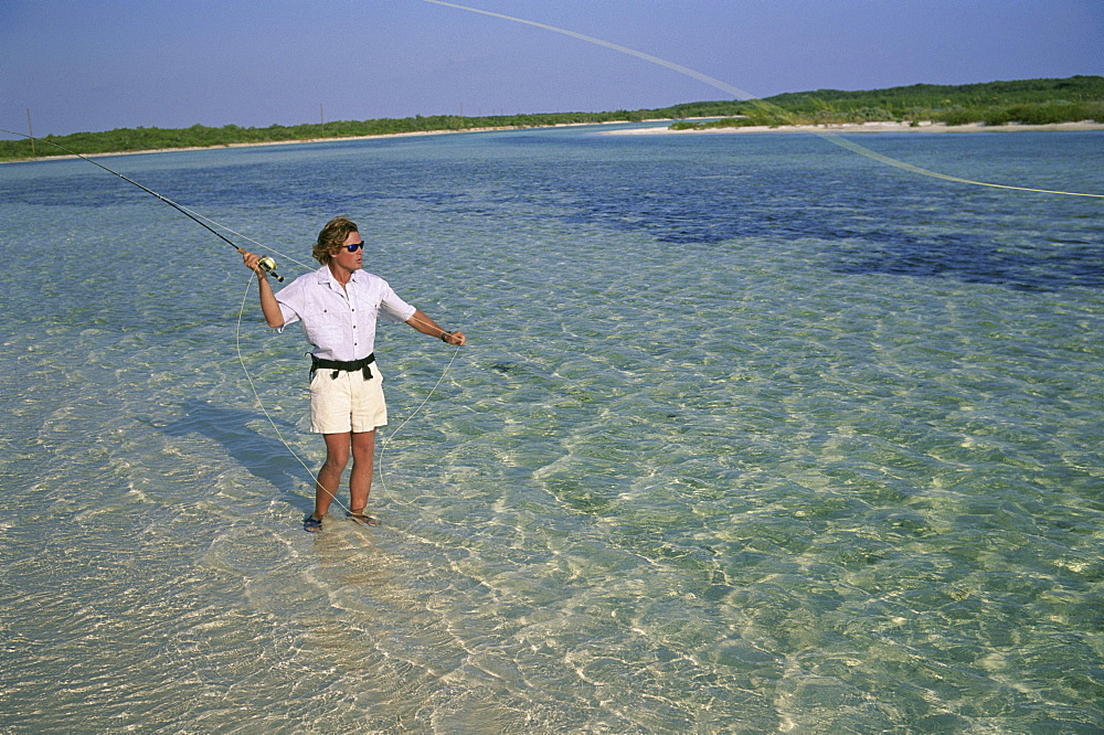 A fly-fisherman casts to a bonefish on Crooked Island in the Bahamas.