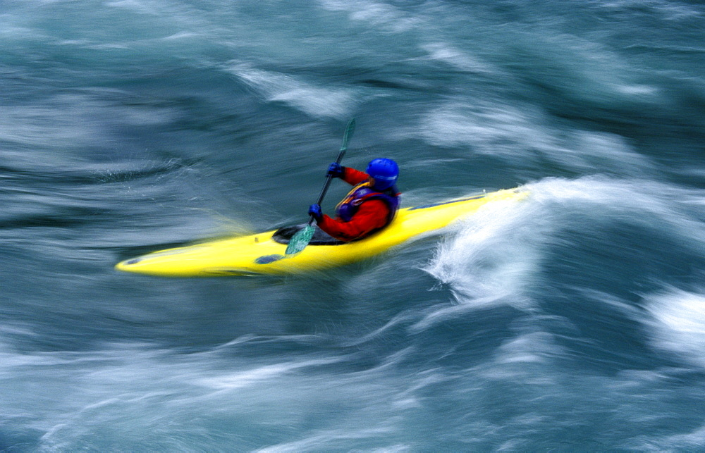 A single kayaker plays in the waves and currents of a glacial river in Kananaskis, Alberta on September 20th, 2000. Kananaskis is a tourist destination that is popular for the stunning scenery, abundant wildlife and adventure sports.