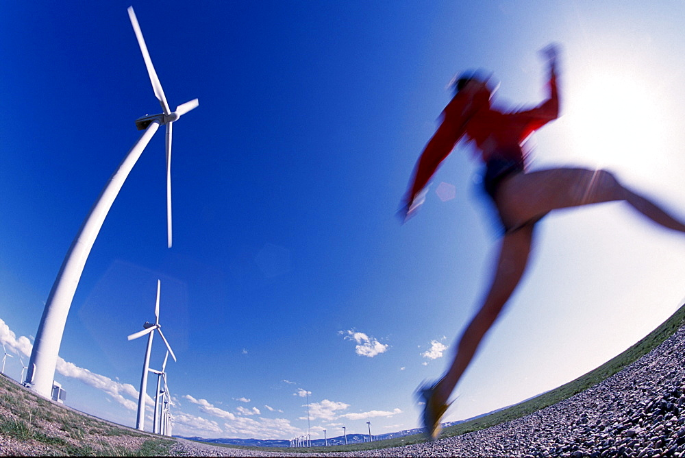 Katie Coddaire running next to a row of wind turbines in Arlington WY.