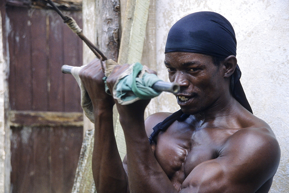 Cuban boxer, Rafael Perez, trains on equipment he constructed from discarded tractor and truck parts, in his home made gym in the yard of his small ramshackle house in Vinales, Cuba.