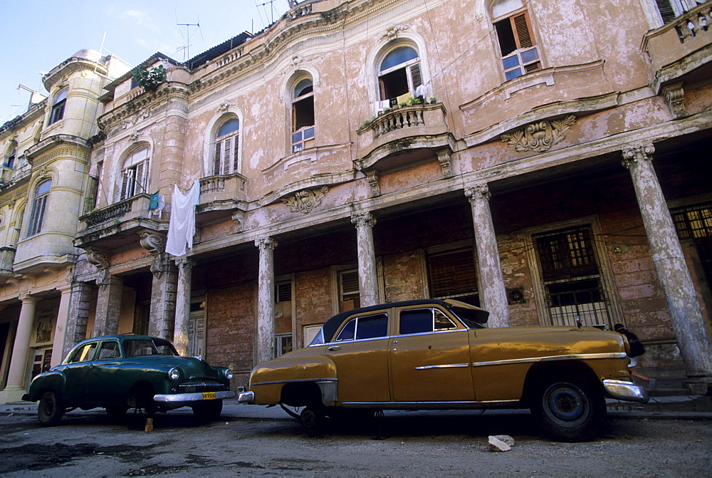 Vintage American cars sit on blocks below a deteriorating building from the Colonial era in Old Havana.  Because of the blockade and economic hardships, cars are a precious possession and many are passed down from generation to generation.