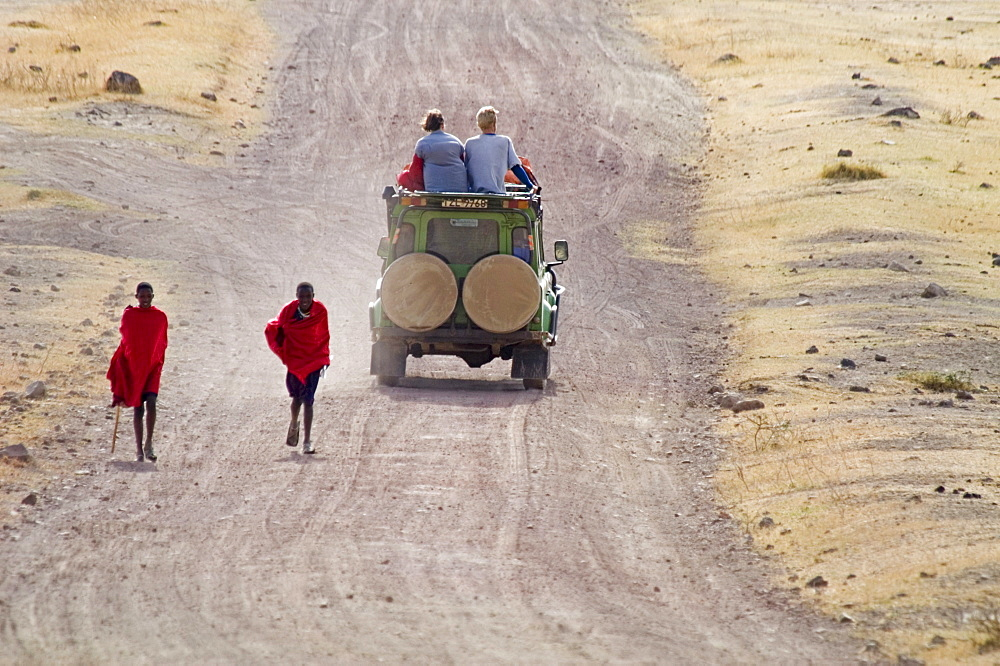 A clash of cultures and centuries: Masai teenagers walk past Western tourists on safari in Ngorngoro National Park, Tanzania. - 857-31323