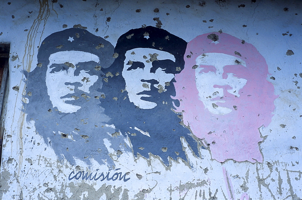 """Painted images of Ernesto """"Che"""" Guevara stare from a pock-marked wall in La Higuera, Bolivia, Saturday, Nov. 13, 2004. Guevara was captured by the Bolivian army in 1967 in a nearby valley and executed in La Higuera days later. Guevara and fellow communist guerillas were attempting to launch a continent-wide revolution modeled on Guevara's success in Cuba in the late 1950s. The Bolivian government recently began promoting the area where he fought, was captured, killed and burried for 30 years as the """"Ruta del Che,"""" or Che's Route."""