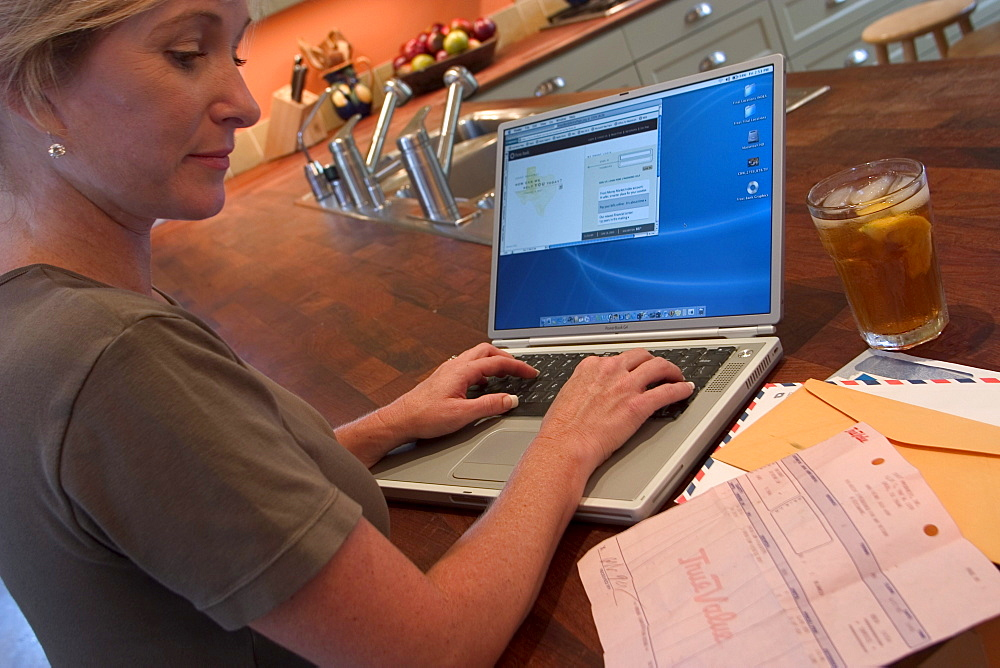 A woman works on her Apple labtop on her kitchen table.