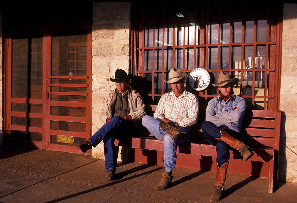 Three cowboys sit on a red bench and enjoy the warmth of the sun.