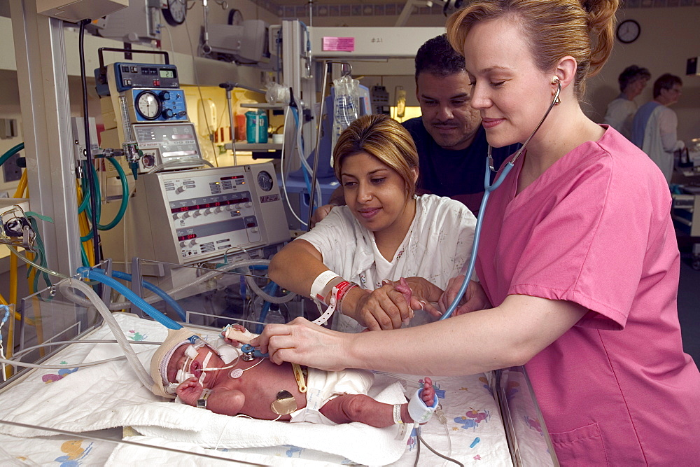 A nurse checks vital signs on a  premature child as it rests.