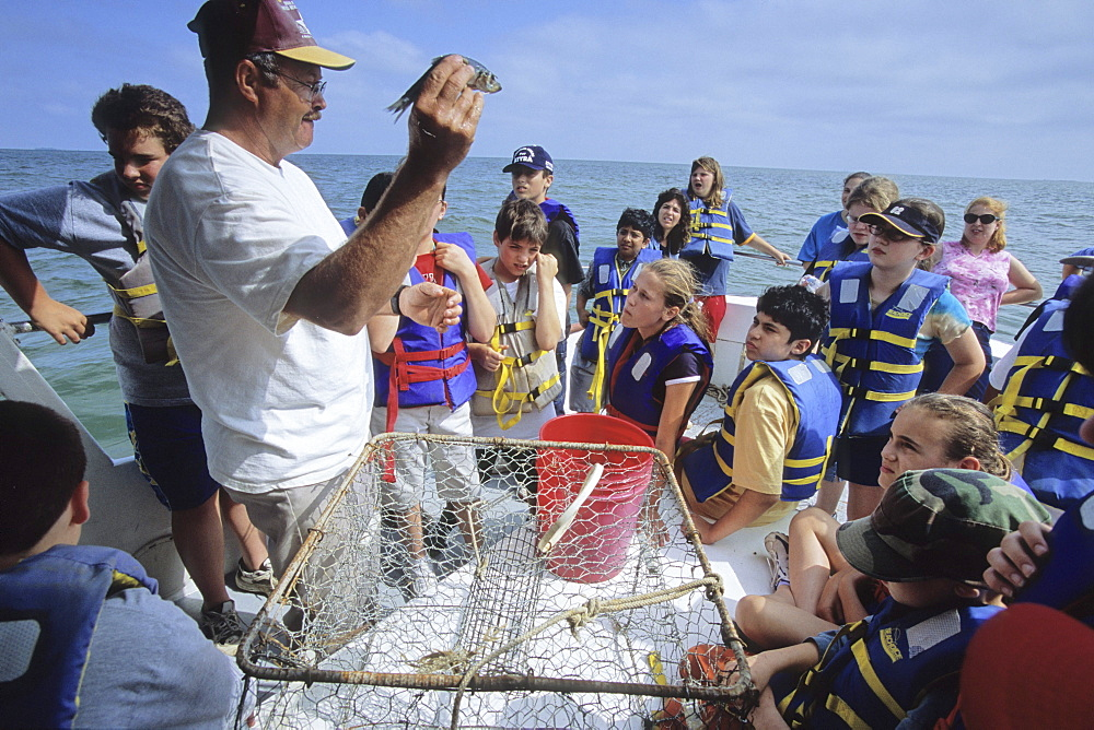 A former waterman and now a worker for the Chesapeake Bay Foundation demonstrates how to bait a crab pot for sixth grade students near Tangier Island, VA