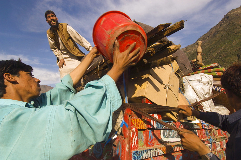 At the Meira tent camp for earthquake survivors, Pashtun men load their family's possessions onto a tractor trailer as they prepare to leave the camp, where they have spent the winter, the Allai  Valley, Northwest Frontier Province, Pakistan.