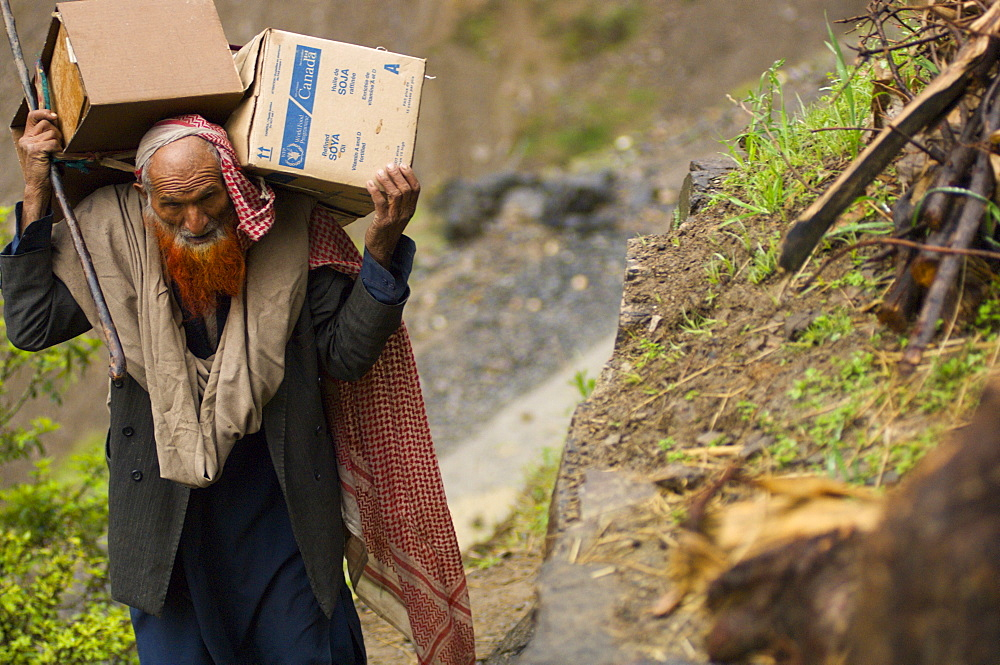A Pashtun man returning home to his mountain home from a camp for earthquake survivors, carries boxes up a steep hill, in the Battagram District, Pakistan's Northwest Frontier Province.  The Pakistan army has dictated that all camps for people displaced by the earthquake be emptied by early April, whether families want to return or not.  The Battgram district was one of the worst-hit by the October 2005 earthquake, and aftershocks and  heavy rains continue to trigger landslides, which have hampered reconstruction efforts and the return of earthquake survivors  to their mountain villages from the low altitude tent camps where many spent the winter.
