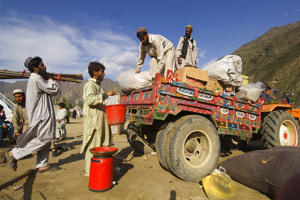 At the Meira tent camp for earthquake survivors, Pashtun men load their family's possessions onto a tractor trailer as they prepare to leave the camp, Allai  Valley, NWFP, Pakistan.