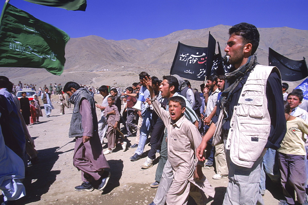 Schoolboys chant and carry banners  to the shrine in the Panjshir Valley of the famous Tajik commander, Ahmad Shah Masood, on the one year anniversary of his assasination, September 9 2002.  Masood was a revered mujahedin leader who also was one of the leaders of the Northern Alliance which opposed the Taliban and helped the US Military in their defeat.  Masood was assasinated by what are thought to be Al Queda operatives on Sept. 9, 2001.  A shrine has been erected in the Panjshir  Valley  from where he led much of his resistance to both the Soviet and Taliban forces, to honor this latest of Afghan war heros.