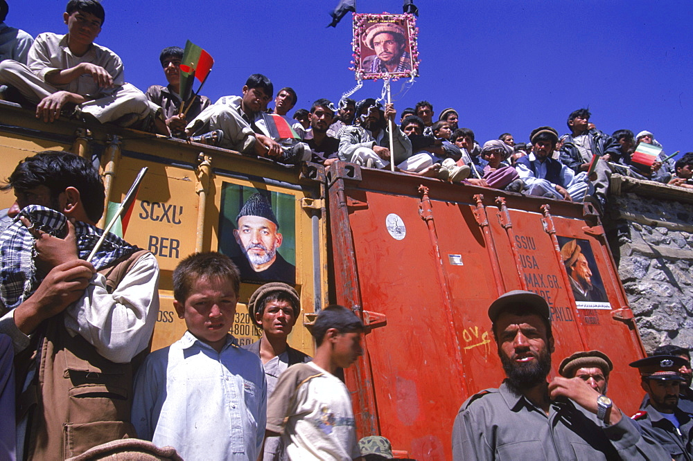Crowds of boys and men, holding  posters of Ahmad Shah Masood and Afghan president Hamid Karzai, line the roofs of buildings during a ceremony in the Panjshir Valley  on the one year anniversary of Masoods assasination, September 9, 2002. Thousands  of pe
