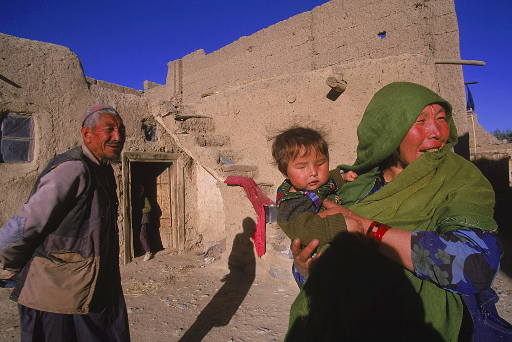 Striking Mongol features distinguish the face of Hamir Mohammed, his daughter and grandson  (who is blind), all living in the ruins of the Qala-i-Dokthar (Daughter's Castle), outside of the town of  Bamiyan, August 30, 2002.  Most of the old town was destroyed and up to 20,000 people of the region might have perished when Bamiyan fell to the Taliban in 2001. Bamiyan Valley is located in the Hazarajat at the edge of the Koh-i-Baba range , the end of the Hindu Kush.  Bamiyan was a prosperous Buddhist kingdom on the ancient Silk Road until the 10th century, when the region  was converted to Islam; in the 12th century, it was destroyed by Ghengis Khan. Most of the people of this region are of the Hazara tribe, and are Shi'a Moslems who have been persecuted for centuries by many of the Pashtun rulers of Afghanistan, who are from the Sunni sect.  They most recently suffered at the hand of the Taliban, who tried for years to ethnically cleanse the region of its Shi'a people