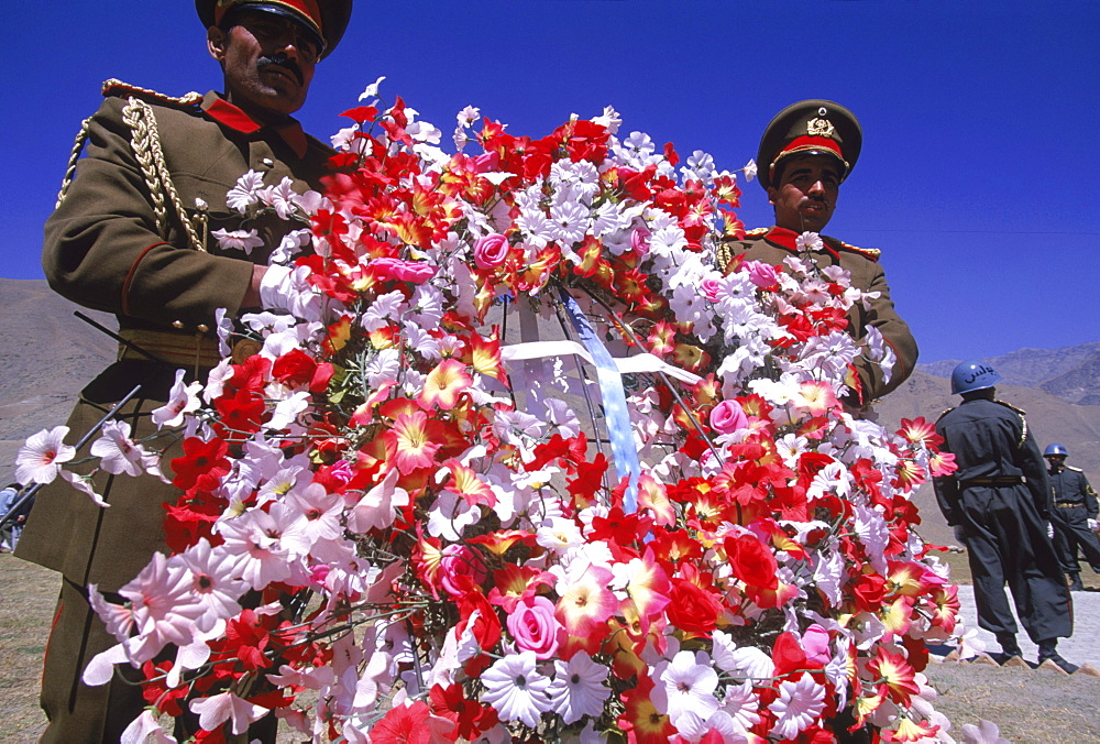 Elaborate flower wreaths are brought by Afghan soldiers as tokens of respect to  the shrine of Ahmad Shah Masood, on the one year anniversary of Masoods assasination, at a ceremony in the Panjshir Valley, Afghanistan, September 9, 2002. Masood was a rever