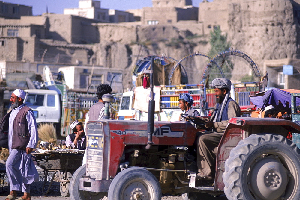 A tractor drives through a bustling market that flourishes below the old city walls in the town of Ghazni, Afghanistan.