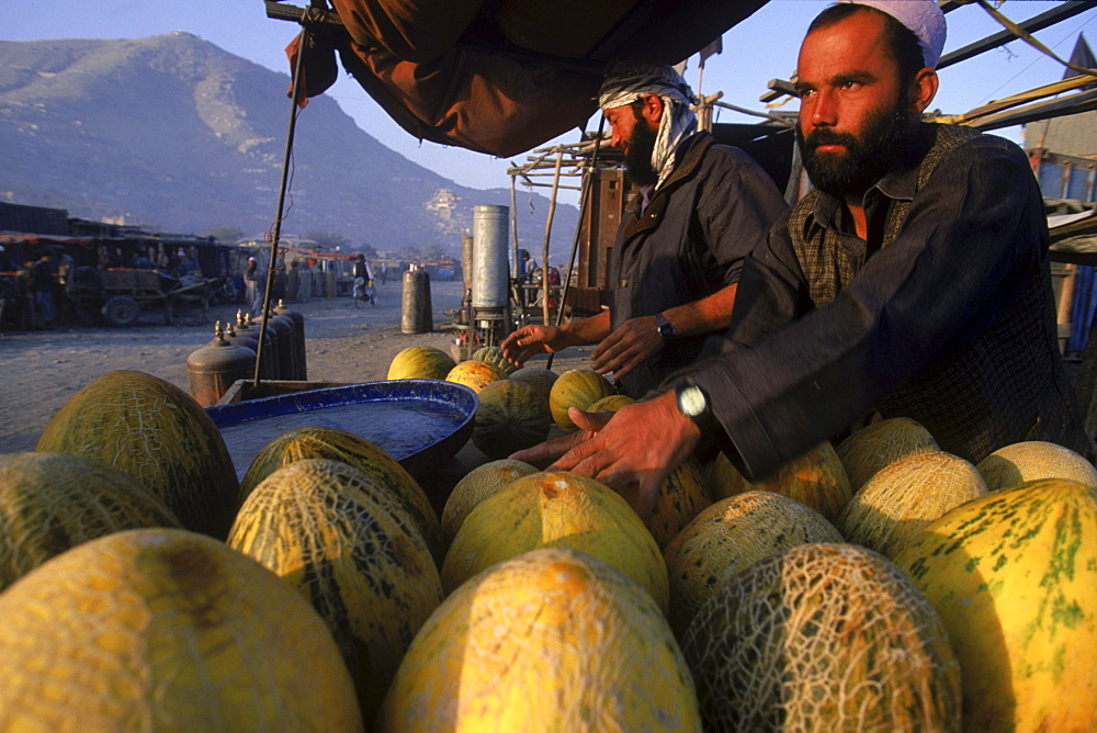 Men sell melons, an Afghan specialty, along the partly ruined streets of  Kabul, Afghanistan. Since the fall of the Taliban regime in late 2001, commerce has thrived in Kabul, if not in all the regions of Afghanistan.  Agricultural products remains one of