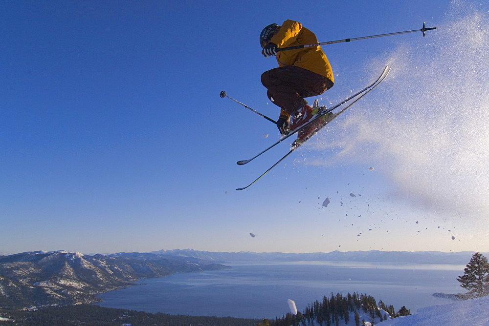 A man jumping on skis above Lake Tahoe in California.