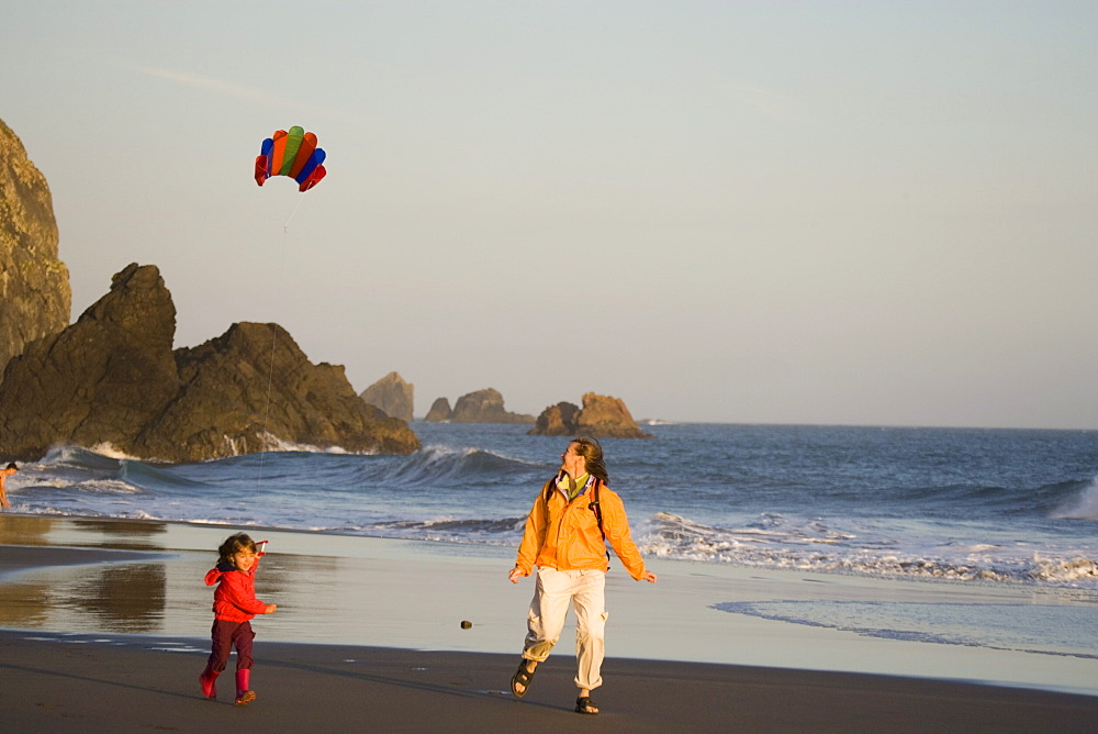 Young mother and daughter fly kite on beach, Harris Beach State Park, Oregon, USA