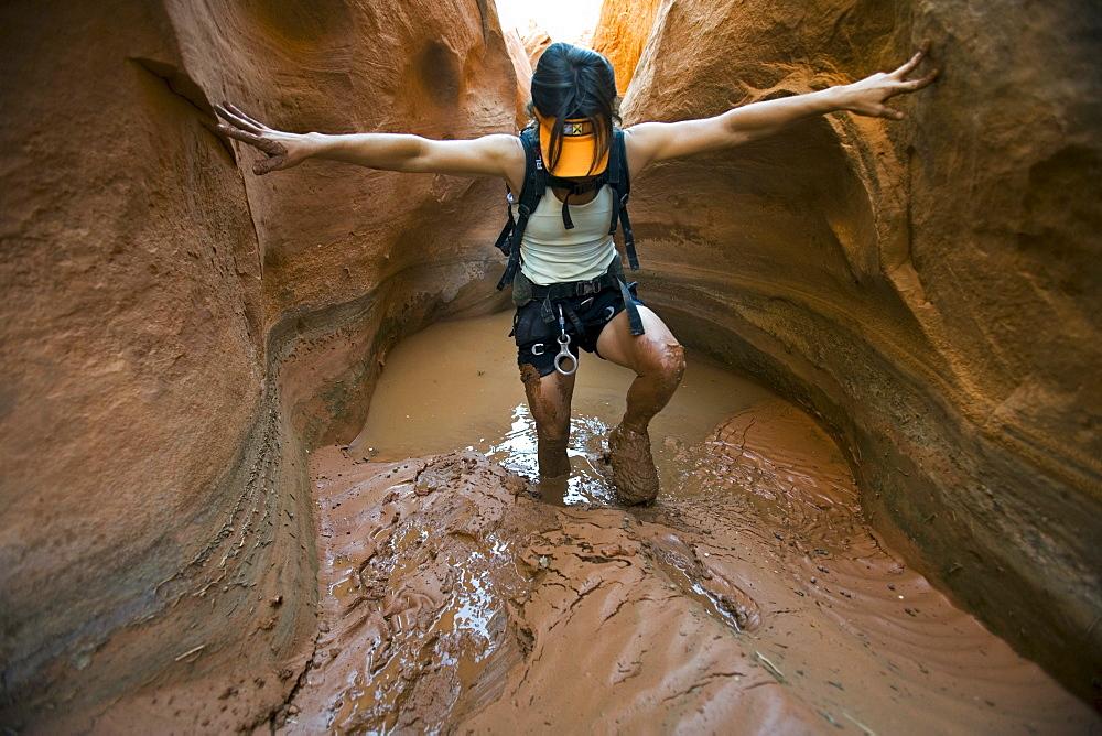 A woman hiking through mud in canyon, Utah.