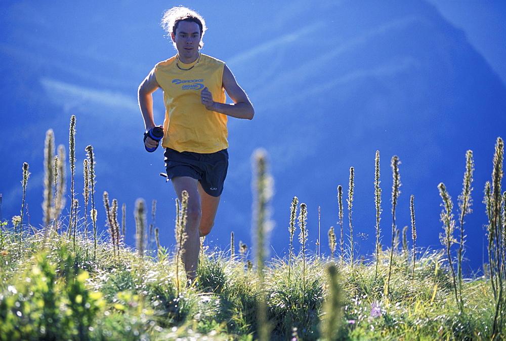 Man running in a yellow shirt in the Cascade Mountains, Washington (Back Lit).
