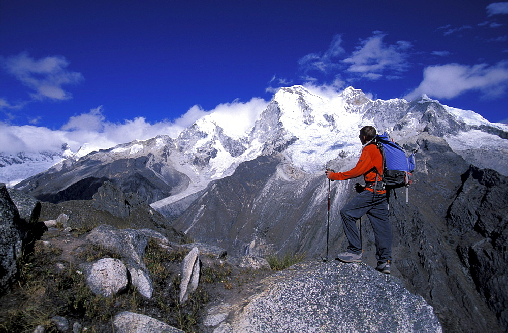 Man standing on a peak looking out at snow covered mountains in Cordillera Blanca, Peru.