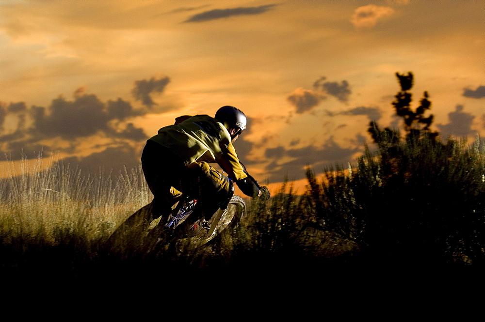 A mountain biker hits a corner at sunset in Kamloops, British Columbia.