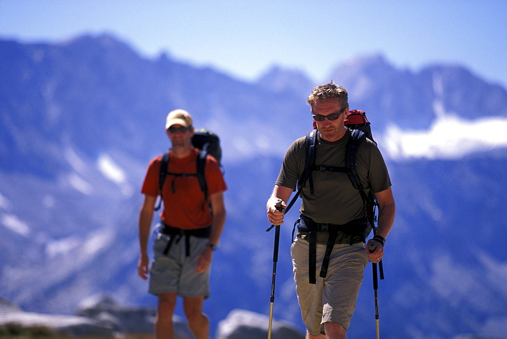 Two hikers trekking through an alpine meadow in Eastern Sierra Nevada mountains, California.