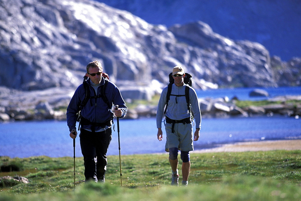 Two men backpacking in an alpine meadow with a lake in Eastern Sierra Nevada mountains, California.