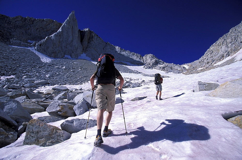 Two backpackers hiking up a snow covered slope in Eastern Sierra Nevada mountains, California.