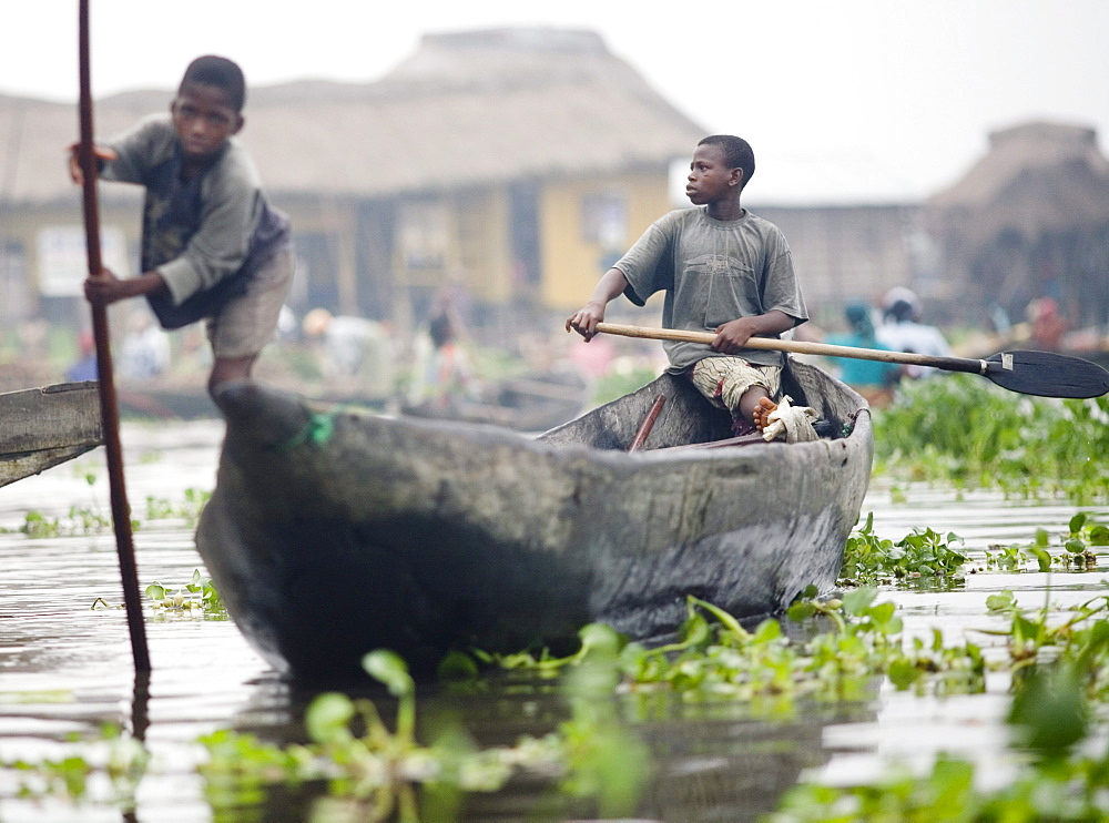 Young boys canoe through the village of Ganvie