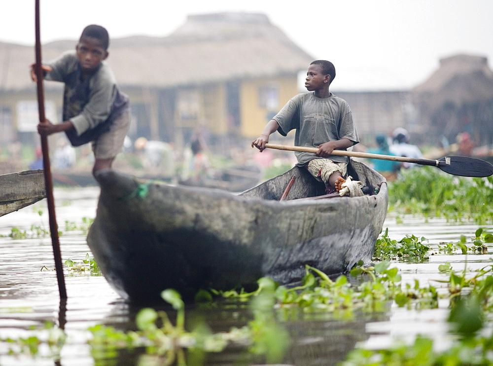 Young boys canoe through the village of Ganvie