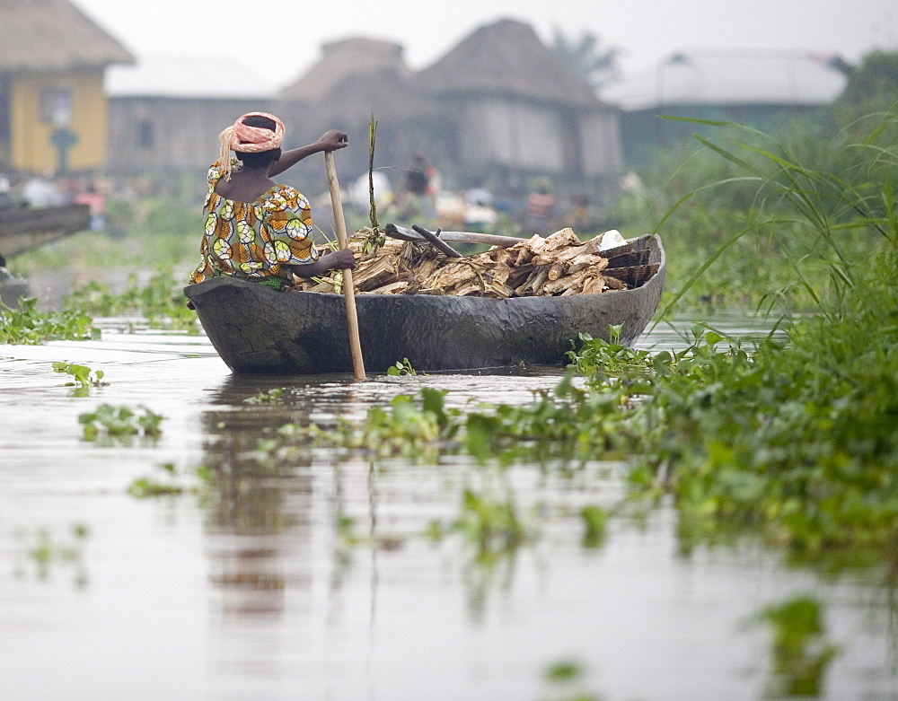 Woman paddles canoe filled with fire wood