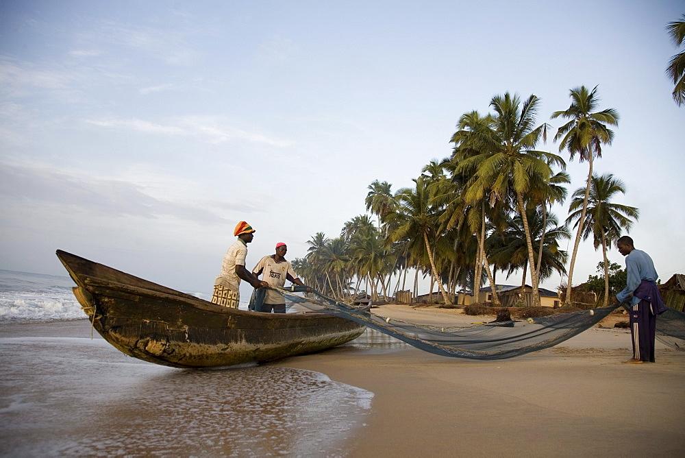 Fishermen pulling nets on a beach in Ghana