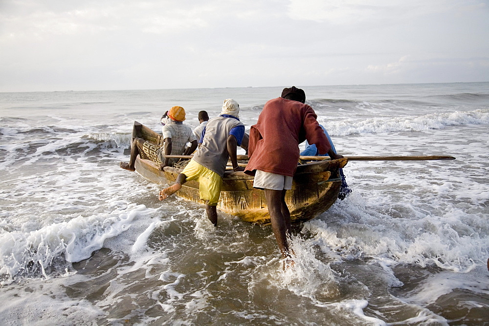 Fishermen pushing a boat into the ocean in Ghana