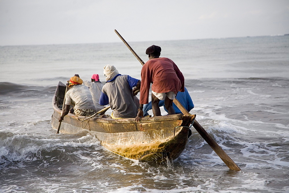 Fishermen in a boat getting into the ocean in Ghana
