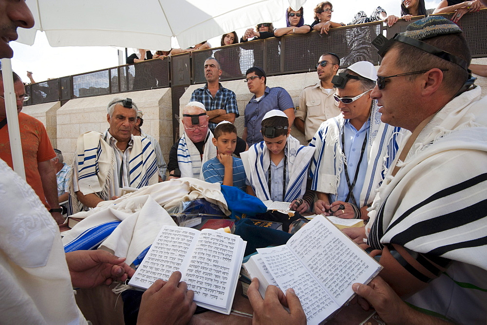 Men read from the Torah at a boy's Bar Mitzvah which is being celebrated in front of the Wailing Wall.