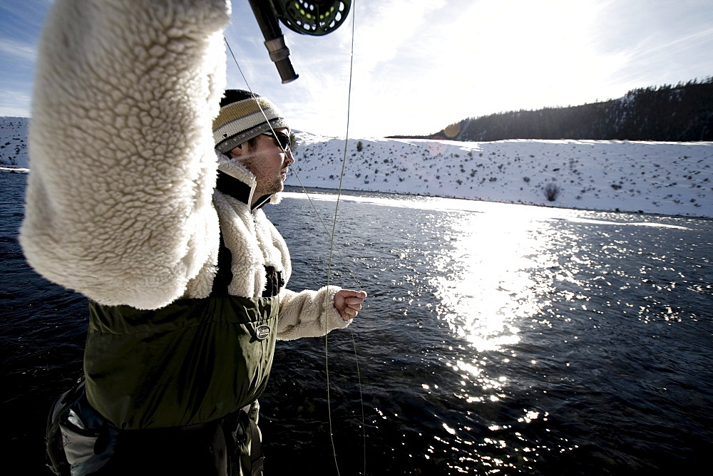 A man out fly fishing on a winter day.