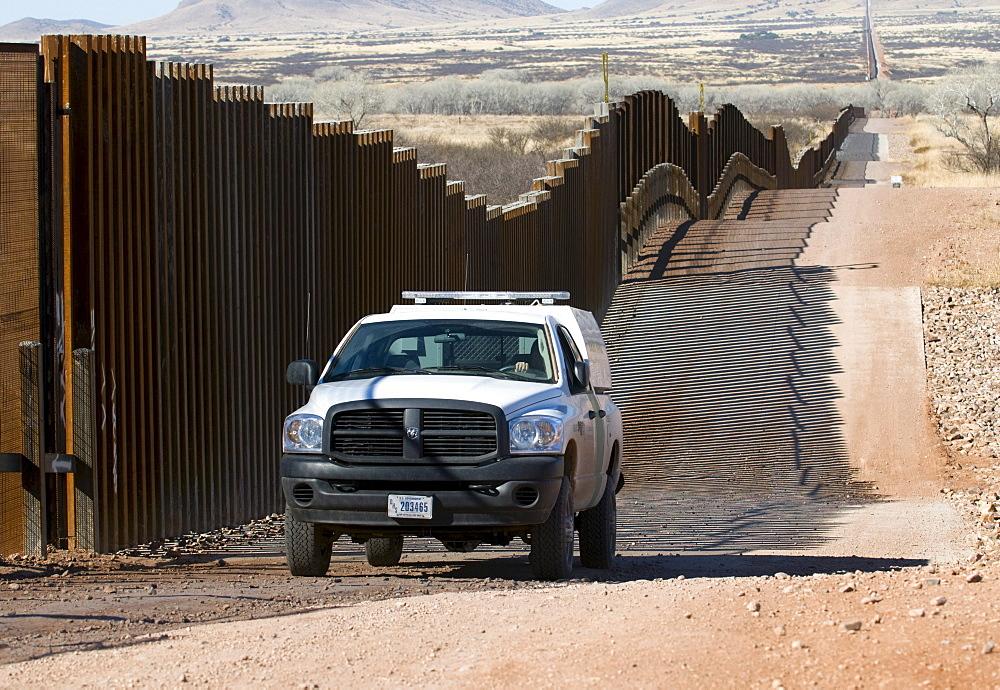 A US border patrol drives the new pedestrian fence on Mexican border, AZ.