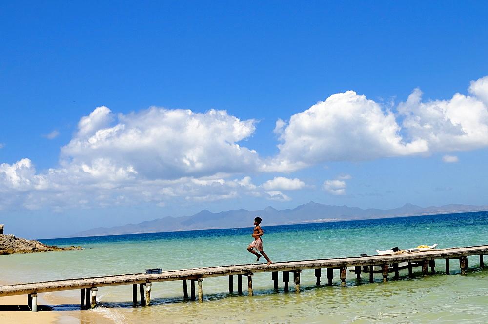 Young boy runs down dock on the Caribbean Island of Cubagua in Venezuela.