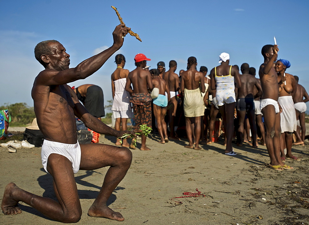 A man kneels in the sand while holding up an offering to the spirits during a voodoo festival on a beach in Haiti.