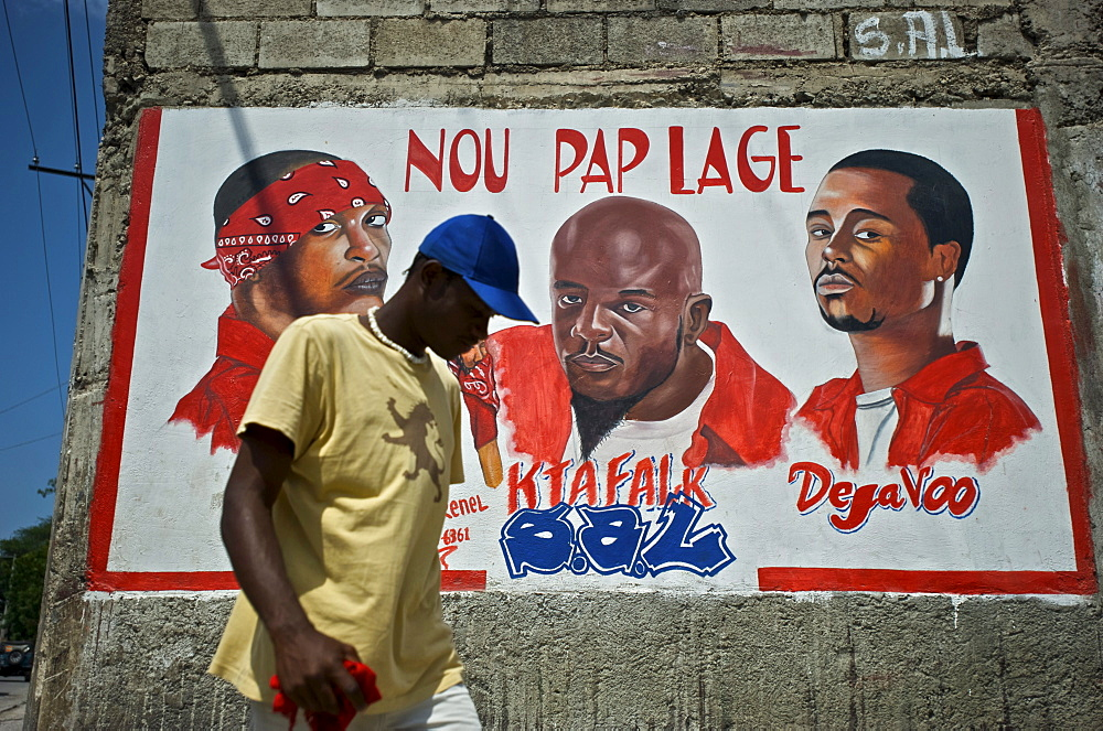 A man walks past a mural dedicated to the deceased members of the rap kreyol group Barikad Crew, in Port-au-Prince, Haiti.