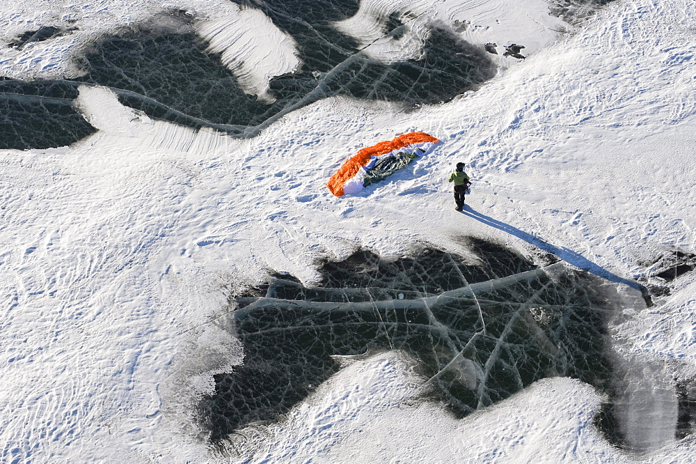 A snowkiter setting up their snowkite on the frozen Missouri River in North Dakota.