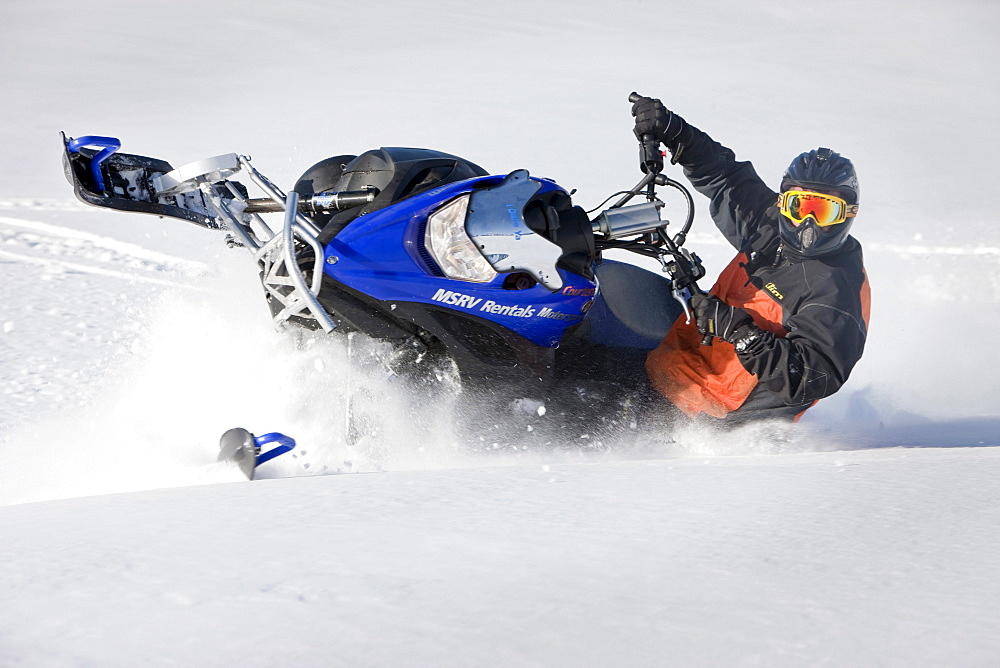 A man makes a sharp turn through powdery snow while snowmobiling on Owlshead Mountain.