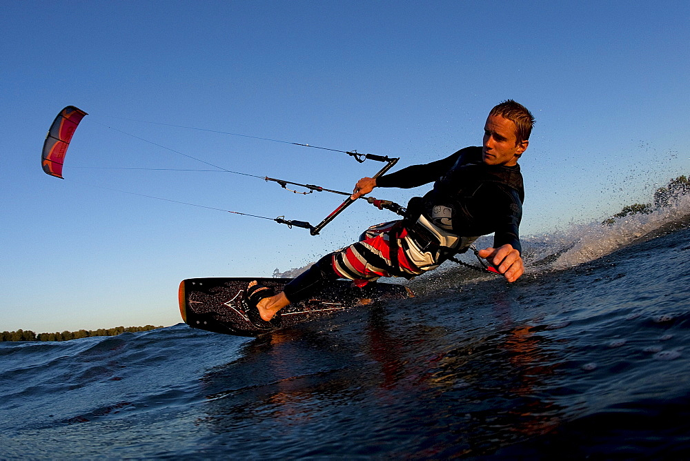 Low angle perspective of a kiteboarder carving by in nice light.