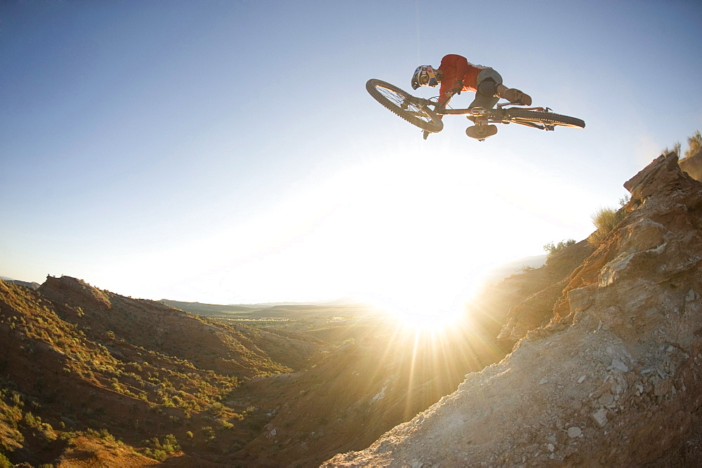 A mountain biker jumps off of a desert slope against bright sun flares in Hurricane, Utah.