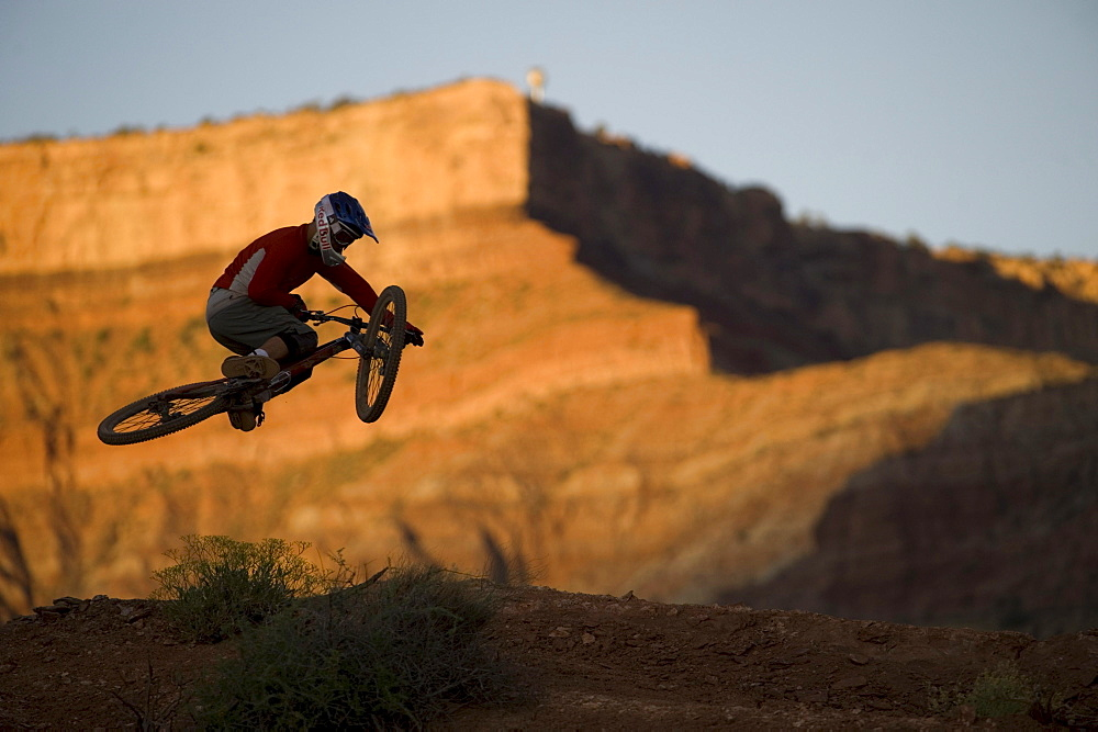 A mountain biker twists as he jumps over a hill in Hurricane, Utah.