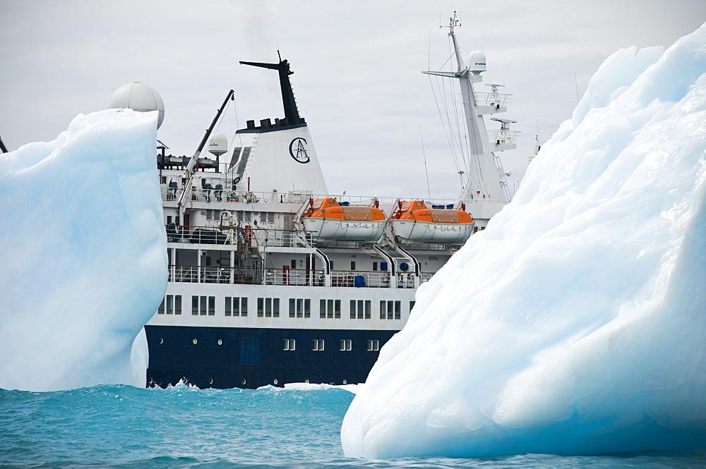 The polar cruise ship the Clipper Adventurer seen between icebergs, Gold Harbor, South Georgia.