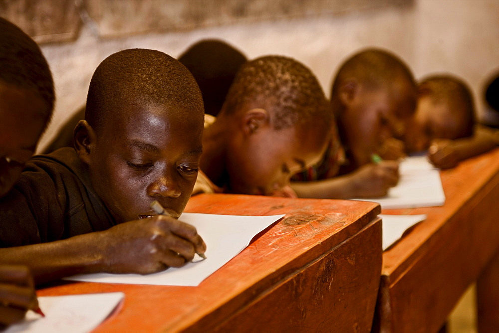 Boys work at their desks in a Rwandan school house.