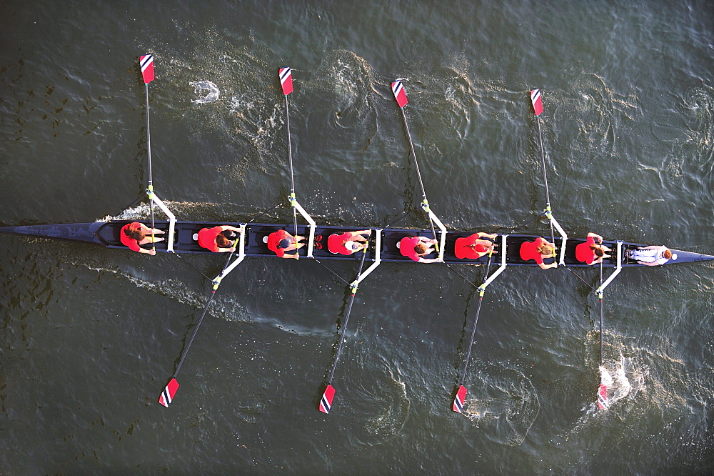 An aerial perspective of a crew of women rowers in a boat crewing down the Tennessee River at sunset.